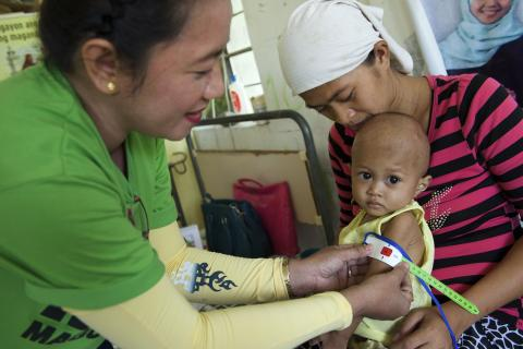 A health worker measures the circumference of a child's upper arm using a mid-upper arm circumference (MUAC) tape to determine the child's nutrition status. The pointer of the tape is in the red figures range, which means that the child is thin for their height.