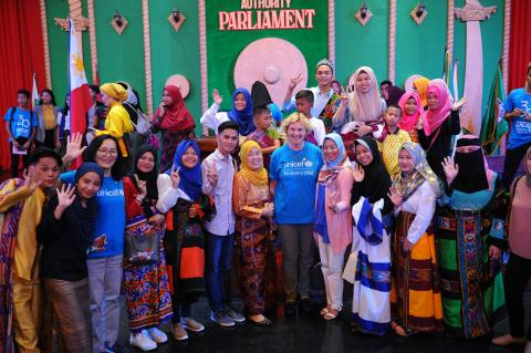 UNICEF staff and children stand onstage at the Bangsamoro Transition Authority Parliament