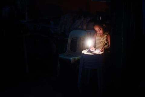 A girl doing homework in the dark, with only a candle providing light