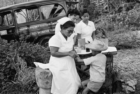 Nurses from a BCG vaccination team tests a boy for tuberculosis, at a table set up near a tree where their truck is parked, in the province of Batangas. 1956.