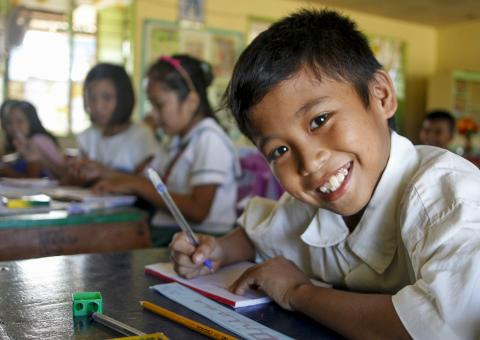 A boy smiles as he writes in class