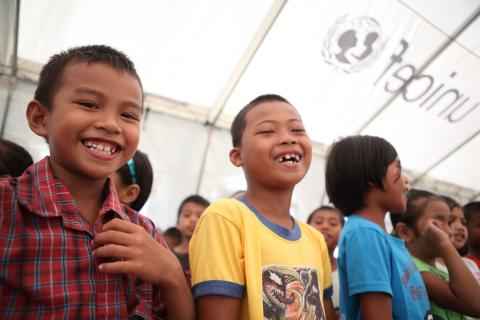 Children smiling while inside a UNICEF tent