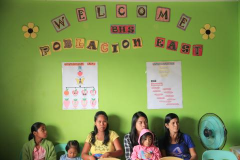 Mothers, caregivers and their children sit inside a health center