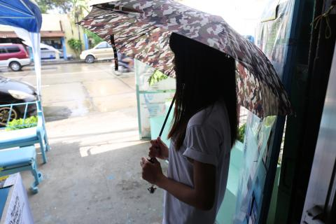 A girl stands outside a health clinic holding an umbrella, with her face and identity hidden by the umbrella's shadow.
