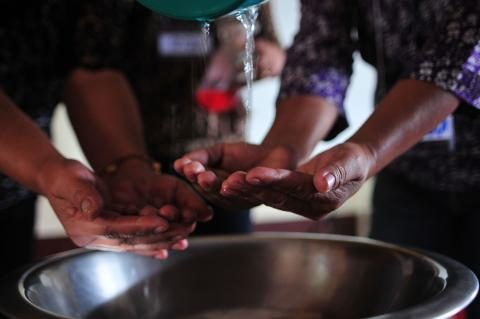 Two health workers wash their hands above a water basin