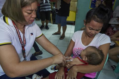 A health worker vaccinates a child while being held by his mother at a health center