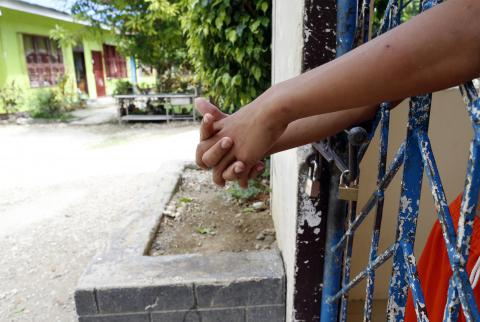 A boy extends his arms from inside a locked gate in a youth rehabilitation centre