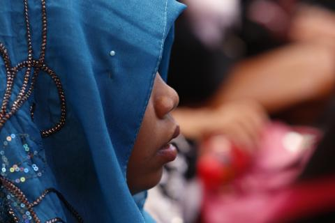 A close-up photo of a child, with her face and identity hidden by a hijab
