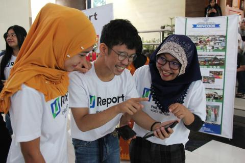 A group of three young people, two girls and one boy, smile as they use an app on a smartphone