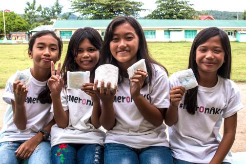 Four girls, wearing t-shirts with the hashtag #MeronAko, holding sanitary napkins