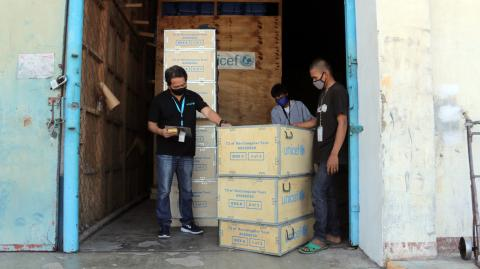 UNICEF staff members inspect boxes of UNICEF supplies