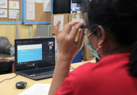 A health worker attends an online webinar on a laptop