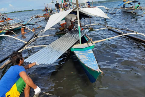 People loading GI sheets on small boats