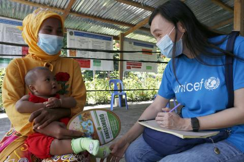 A UNICEF staff member wearing a blue UNICEF-branded t-shirt and a face mask speaks to a parent carrying a baby