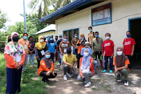 A group of health workers and community members, wall wearing face masks, outside their village hall