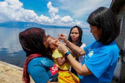 A UNICEF staff member gives a dose of oral polio vaccine to a child