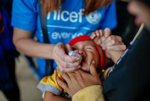 A UNICEF staff member administers a polio vaccine to a child