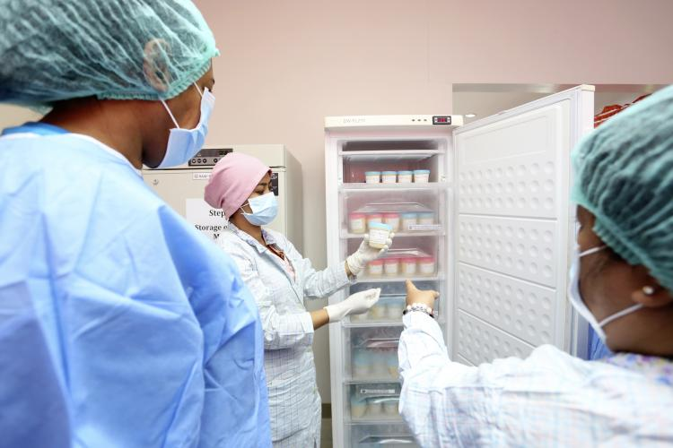 Health workers wearing laboratory gowns, gloves, hair caps and face masks inspect breast milk stored in a refrigerator at a human milk bank