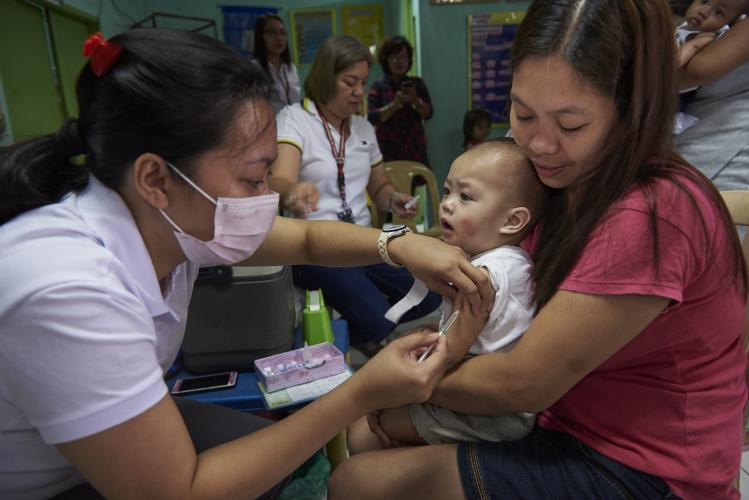 A woman holds her child while a health worker injects an MMR vaccine