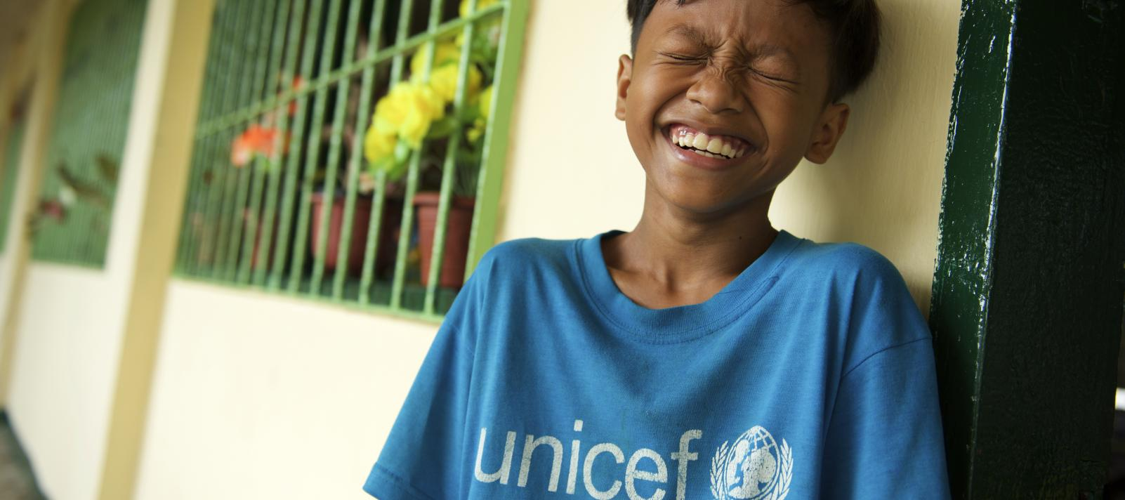 22631d2e6 A boy in a blue UNICEF shirt smiling towards the camera with his eyes closed