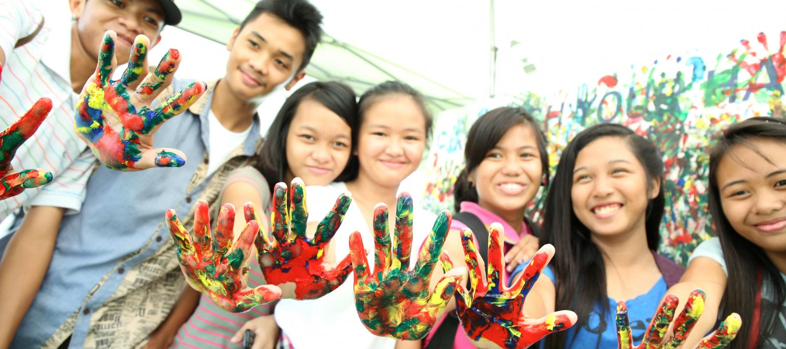 Adolescents show their palms with paint at a mural painting session