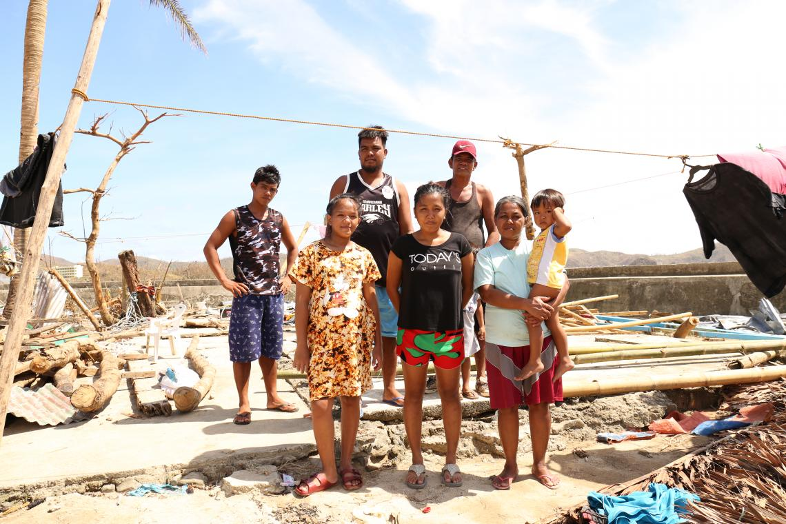 A family in front of their house that was destroyed by Super Typhoon Rolly/Goni