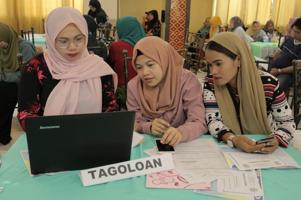 Health workers wearing veils/hijab discuss in front of a laptop computer