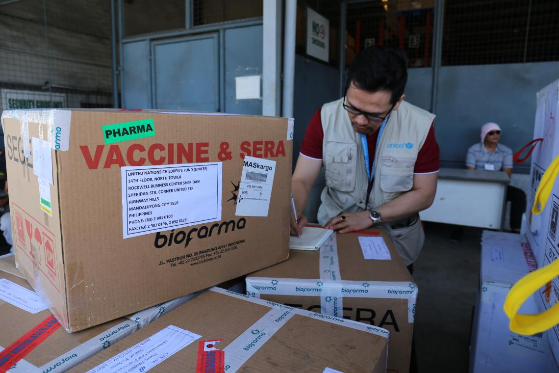 A UNICEF staff member inspects boxes of polio vaccines
