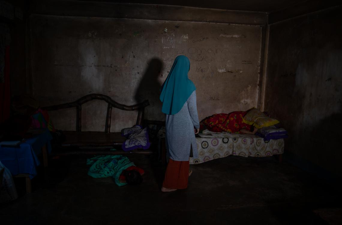A girl wearing a hijab stands in her home, facing away from the camera to hide her face