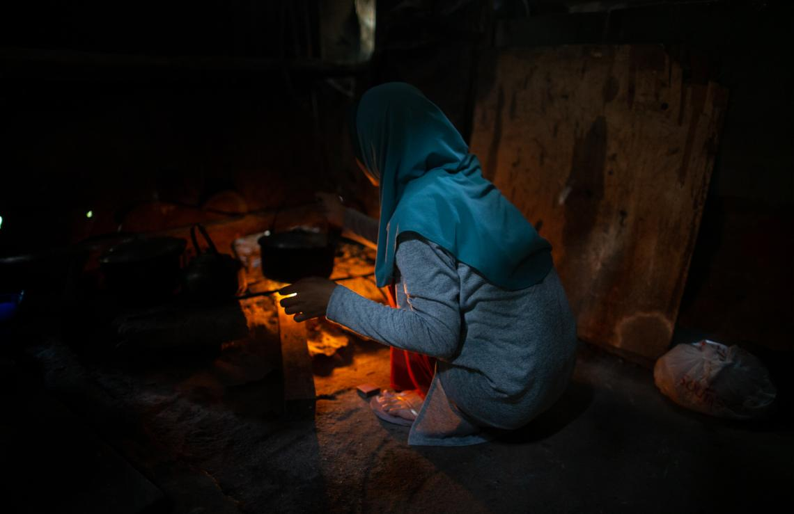 A girl wearing a hijab, her face turned away from the camera, cooks food over a stove in her home