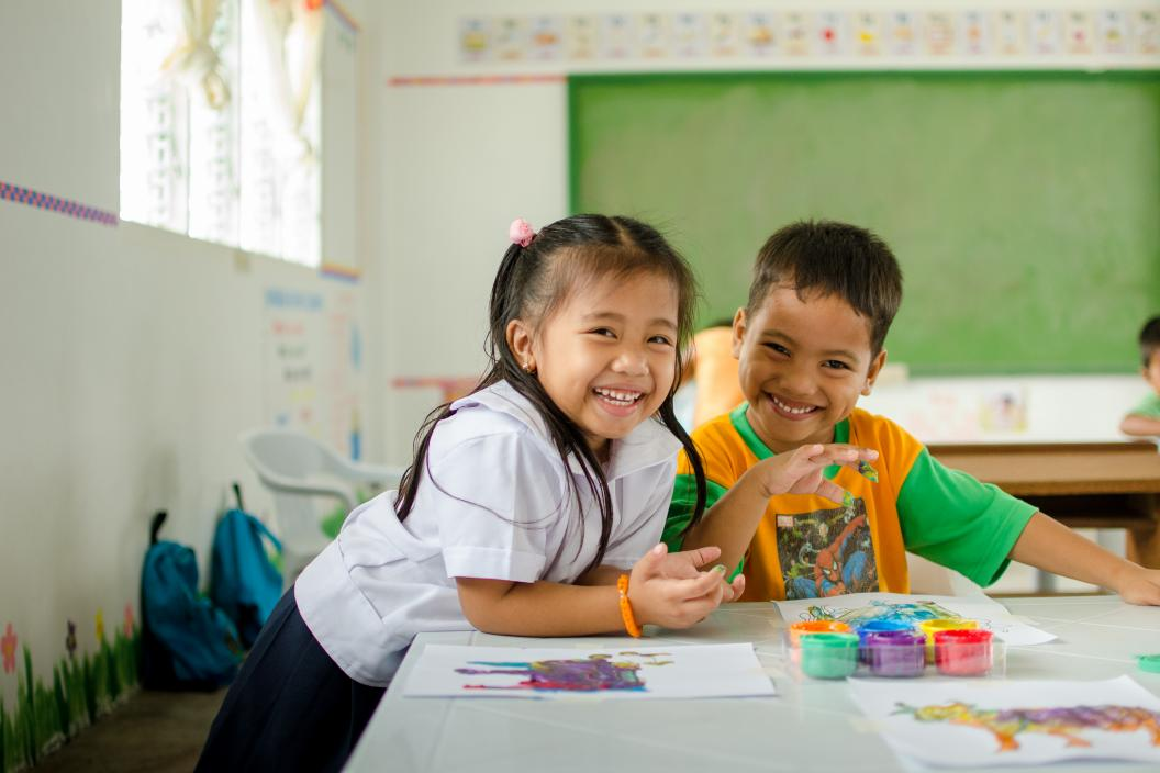 A girl and boy participate in a finger-painting activity inside a classroom