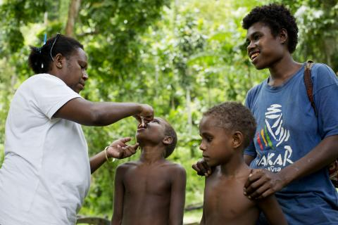 A child being vaccinated while his mother and sibling look on.