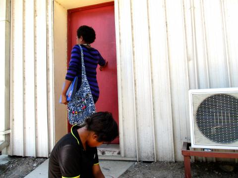 A young girl sitting in front of a classroom door.