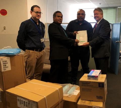 PNG Health Minister, Jelta Wong accepts the PPE from UNICEF Representative, David Mcloughlin