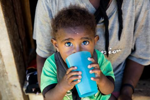One-year-old Otmar gets a daily ration of water, just a quarter of a cup a day, at Pombreal Village in Southern Highlands Province where communities are slowly recovering from February's 7.5 magnitude earthquake and numerous aftershocks that destroyed water sources.
