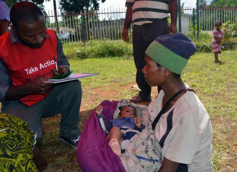 Angela and her son get attended to by a health worker at a child health outreach site.