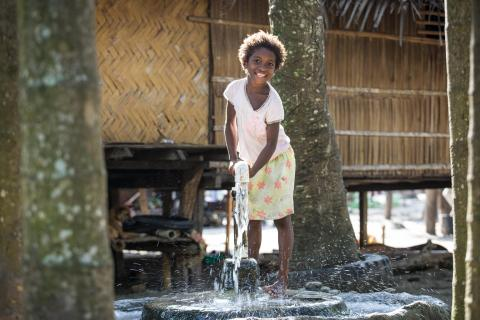A young girl pumps water from an underground water source at Dugumor Village, Bogia District, Madang Province.