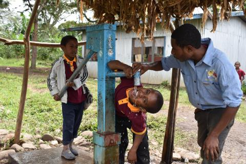 Children drinking water from a UNICEF water pump.