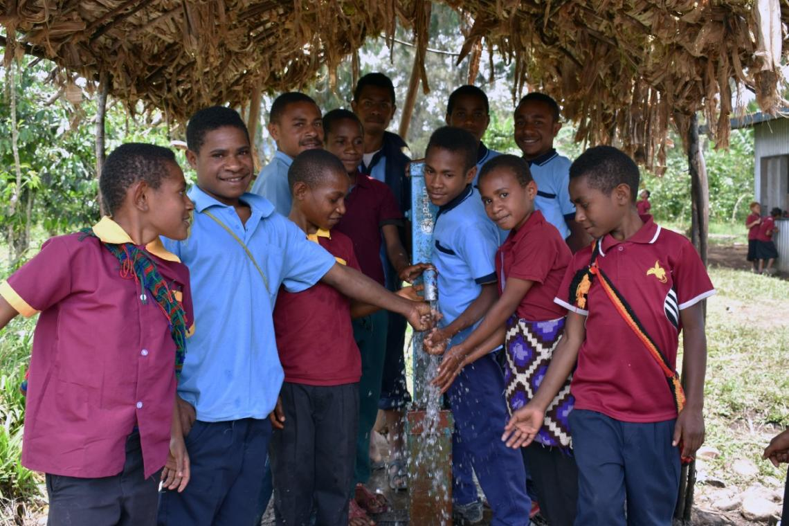 Anselm Primary School students show off the borehole that supplies them with clean water