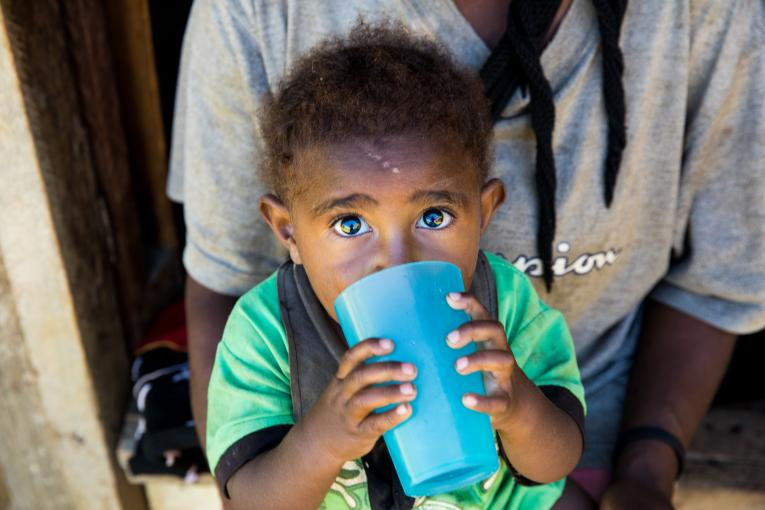 A child drinking water from a cup.