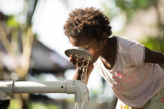 A child drinking water from water pipe at Dugumor Village, Bogia District, Madang.