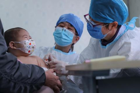 A 6-month baby receives a delayed vaccine shot at a community health centre in Beijing, China, on 26 March 2020.