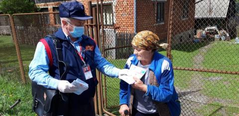 A postman distributes information materials for the prevention of COVID-19, developed by UNICEF in Romania, in Moeciu de Jos, Brașov County, May 5, 2020.n Romania, in vulnerable communities in rural areas. The action takes place as a result of the partnership between the Romanian Post and UNICEF in Romania, which aims, in the first phase, to test the distribution of messages to communities without internet or television access in the counties of Brașov and Bacău.