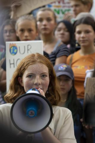 A young girl speaks at a public gathering for children's rights