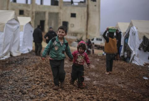 Two children walking in an informal tented settlement, near Alqah village, close to the Syrian-Turkish border, northwest Syria, 30 December 2019.