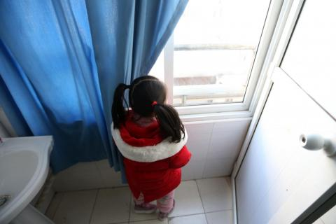 A girl in a red jacket looks through the window outside