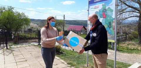 Pieter Bult, the UNICEF Reprezentative in Romania delivers masks to community nurse Cătălina Olteanu, in Secuieni, eastern Romania, on April 15, 2020. This is one of the 35 communities where UNICEF delivered protective equipment to community workers supporting  vulnerable children and their families.
