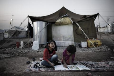 Seated on a rug atop the dirt ground, girls complete homework outside their tent home, in the Kawergosk camp for Syrian refugees, just west of Erbil, the capital of Kurdistan Region