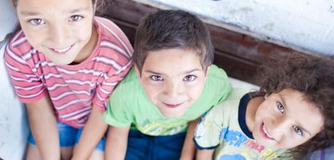 Three children benefiting from the UNICEF Minimum Package of Services smiling to the camera
