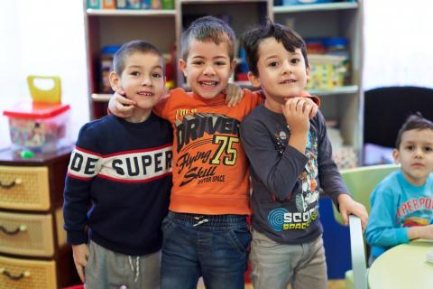 Three boys smiling in class in a Bacau school